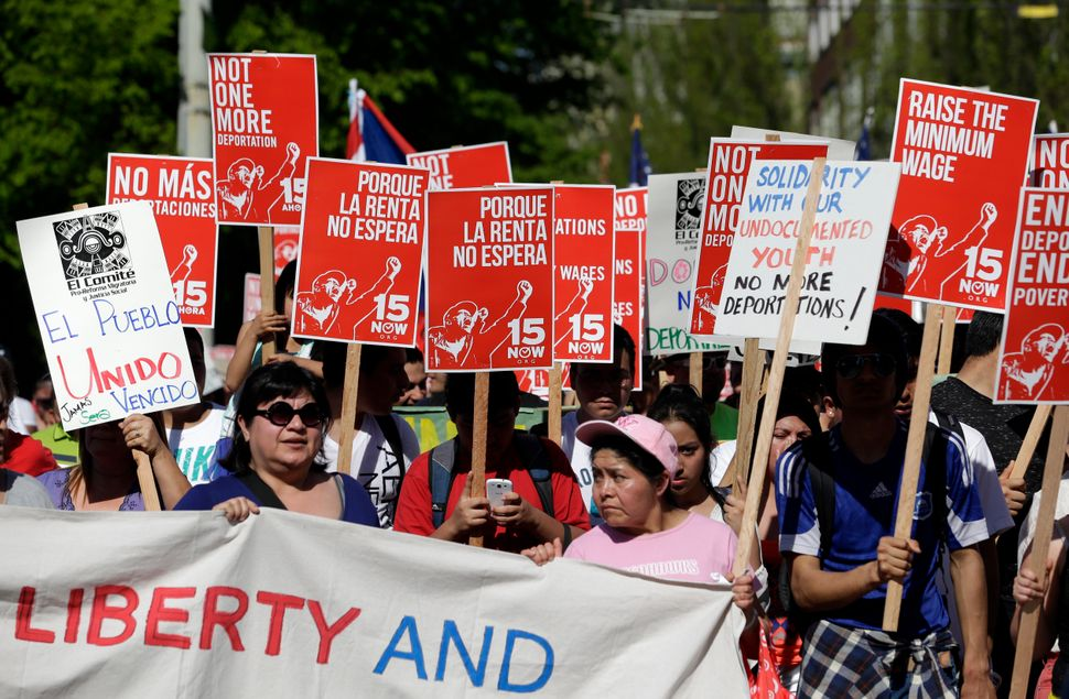 Demonstrators walk toward downtown during a May Day march Thursday, May 1, 2014, in Seattle. Hundreds of people marched peace