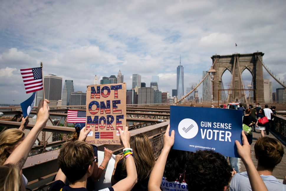 """A demonstrator holding a sign that reads """"Not One More"""" marches across the Brooklyn Bridge to call for tougher gun control la"""