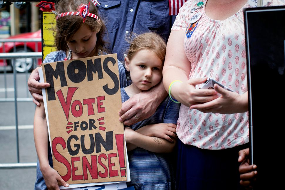 Josie Lando, center, reacts alongside her sister Nora, left, at a rally outside city hall to call for tougher gun control law