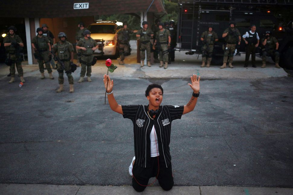 A demonstrator holding a red rose kneels in front of armed police officers and raises their hands above his head during prote