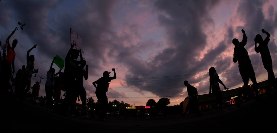 In this Aug. 18, 2014 photo taken with a fisheye lens, people protest for Michael Brown who was killed by police Aug. 9 in Fe