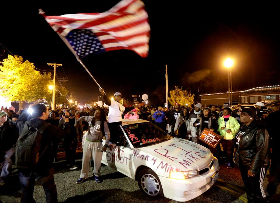 Protesters arrive at the Ferguson Police Department Saturday, Oct. 11, 2014, for a rally in remembrance of Michael Brown in F