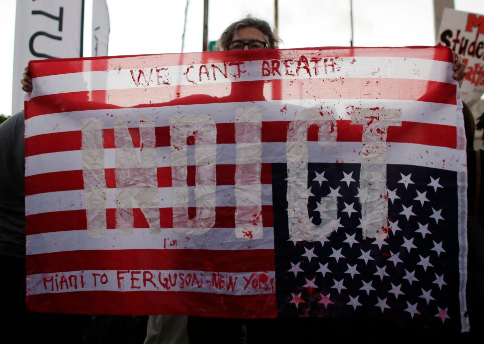 """A protester holds an American flag with the word """"Indict"""", during a protest Friday, Dec. 5, 2014, in Miami."""