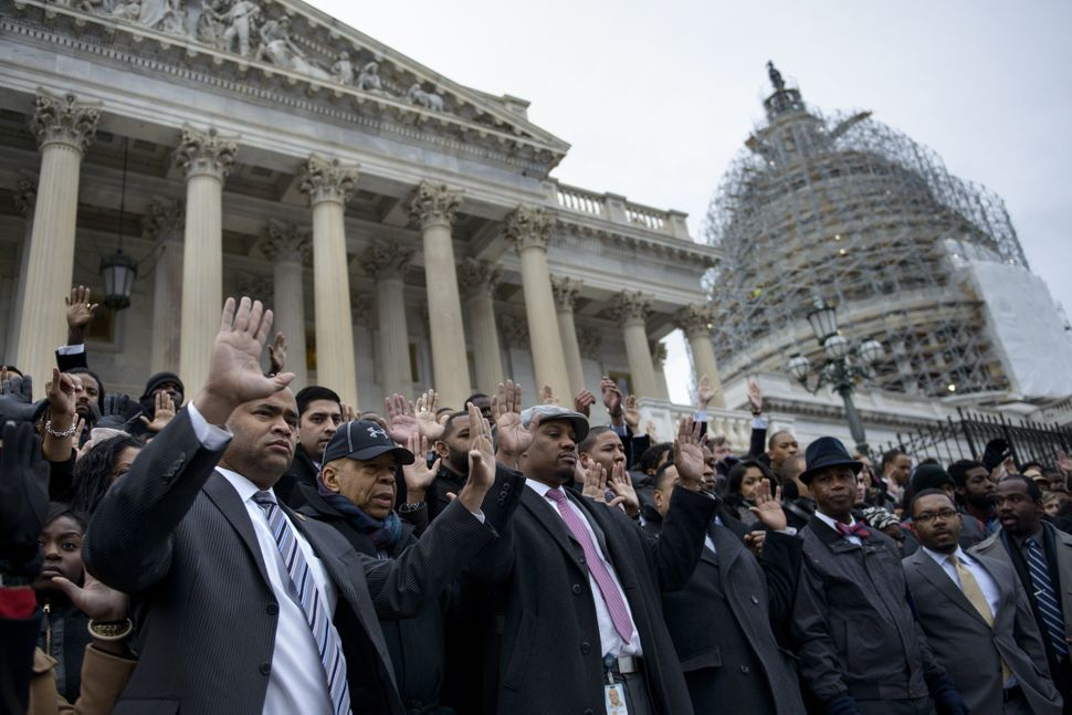 African-American Congressional staff and others hold their hands up during a walk-out outside the House of Representatives on