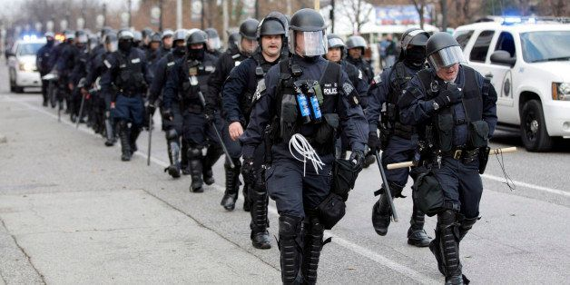 Police wearing riot gear walk past Edward Jones Dome following an NFL football game between the St. Louis Rams and the Oaklan