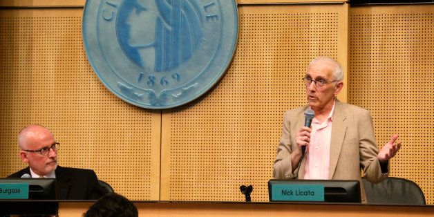 Seattle City Council member Nick Licata, right, speaks next to the seal of the City of Seattle as Council president Tim Burge