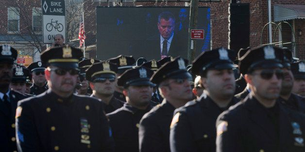 Police officers turn their backs as New York City Mayor Bill de Blasio speaks at the funeral of New York city police officer Rafael Ramos in the Glendale section of Queens, Saturday, Dec. 27, 2014, in New York. Ramos and his partner, officer Wenjian Liu, were killed Dec. 20 as they sat in their patrol car on a Brooklyn street. The shooter, Ismaaiyl Brinsley, later killed himself. (AP Photo/John Minchillo)