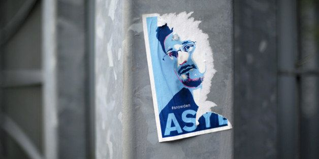 BERLIN, GERMANY  - AUGUST 06: Half ripped of flyer with a portrait of Edward Snowden and the request to grant him asylum on A