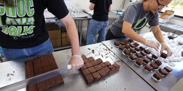 In this Sept. 26, 2014 photo, smaller-dose pot-infused brownies are divided and packaged at The Growing Kitchen, in Boulder.