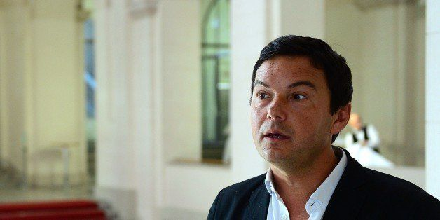 French economist and author Thomas Piketty speaks to journalists as he poses for a photographer following a discussion with G