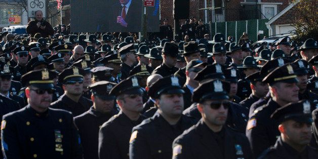 File-This Dec. 27, 2014, file photo shows police officers turning their backs as New York City Mayor Bill de Blasio speaks at