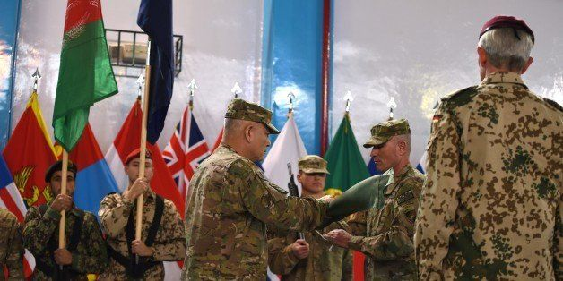 US General John Campbell (C) folds the flag of the NATO-led International Security Assistance Force (ISAF) during a ceremony
