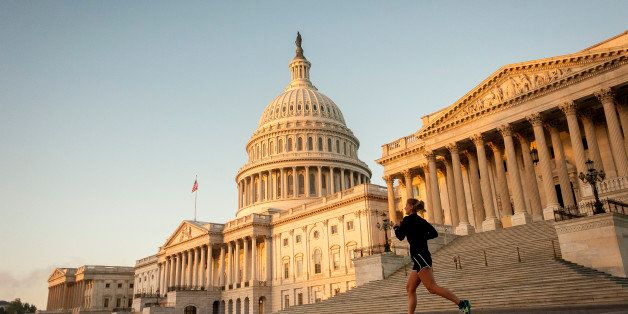 A jogger runs past the United States Capitol building at sunrise in Washington, D.C., U.S., on Tuesday, Oct. 15, 2013. Senate
