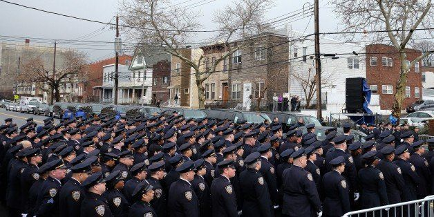 New York Police Department (NYPD) officers pay their respect as the procession of NYPD officer Wenjian Liu passes by in New Y