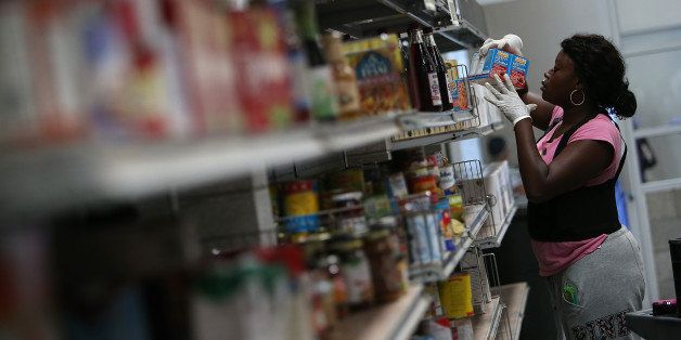 SAN FRANCISCO, CA - MAY 01: A worker stocks shelves with canned goods at the SF-Marin Food Bank on May 1, 2014 in San Francis