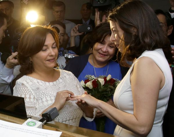 Arguello places a ring on Pareto's finger as her mother, Berta Arguello, looks on holding flowers. The pair, who were wed by