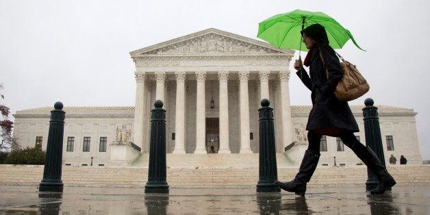 As a steady rain falls, a morning commuter make her way past the Supreme Court in Washington, Tuesday, Dec. 2, 2014. (AP Phot