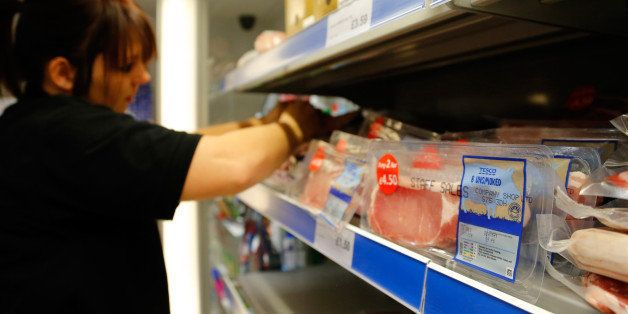 Rashers of Tesco Plc own brand bacon sit in a refrigerated meat cabinet as an employee arranges meat products inside the Comm