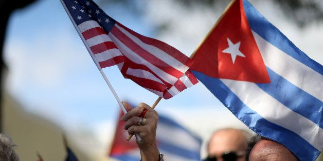 MIAMI, FL - DECEMBER 20: A protester holds an American flag and a Cuban one as she joins with others opposed to U.S. Presiden