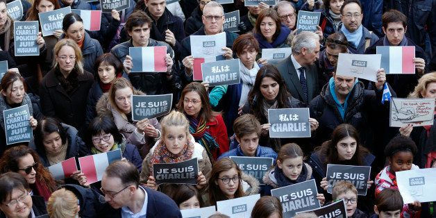 """French residents, their family and Japanese hold """"Je suis Charlie, or I am Charlie"""" signs as they attend a special memorial g"""