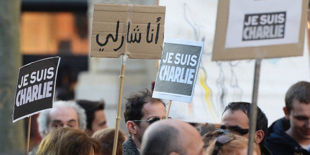 People holds signs that read 'Je suis Charlie' (I am Charlie) in French and Arabic (2nd L) during a rally in Marseille, south