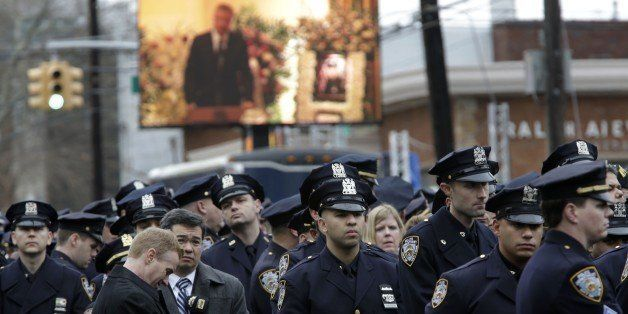 Some police officers turn their back to a large screen that displays New York City Mayor Bill de Blasio speaking during the f