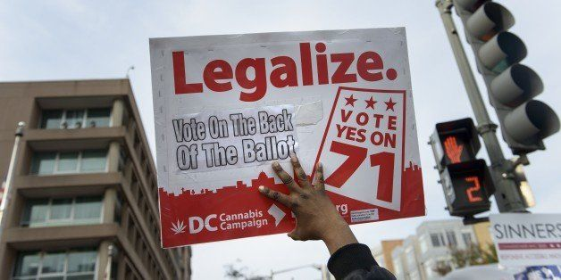 A man holds up a sign for Ballot Initiative #71, the legalization of marijuana, on November 4, 2014 in Washington, DC. Voters