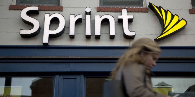 A pedestrian uses a mobile device while walking past a Sprint Corp. store in Washington, D.C., U.S., on Friday, Oct. 24, 2014