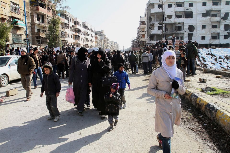Hundreds of Syrians walk on a street with damaged buildings before going out of town to buy food and other essential material