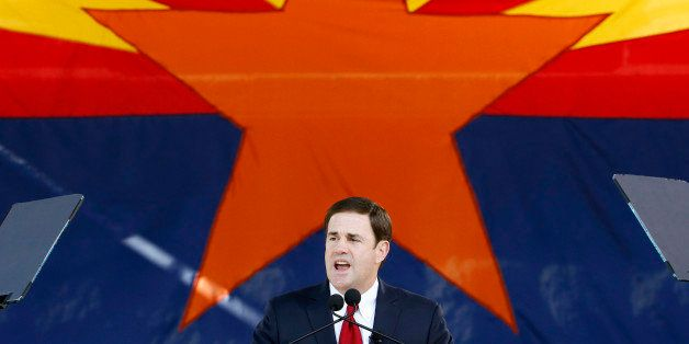 FILE - In this Jan. 5, 2015, file photo, Republican Arizona Gov. Doug Ducey addresses the crowd after being sworn in during inauguration ceremonies at the Arizona Capitol in Phoenix. The Arizona Legislature is putting a bill creating a new high school civics test on the fast track. Gov. Doug Ducey wants the bill to be the first to reach his desk, and the Senate and House education committees have set scheduled hearings for Thursday, Jan. 15, 2015. The bills require students to correctly answer 60 of 100 questions on the civics portion of the test required to become a U.S. citizen in order to graduate. Ducey said Monday that students just aren't learning the basic civics they need to be good citizens. (AP Photo/Ross D. Franklin, File)