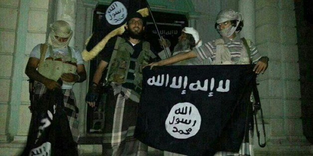 A picture taken with a mobile phone early on May 24, 2014 shows Al-Qaeda militants posing with Al-Qaeda flags in front of a m