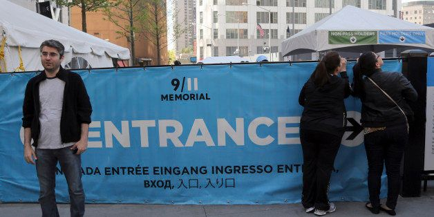 A visitor to the Sept. 11 Memorial, left, poses for a photo as others, right, peer at the entrance line, Saturday, May 4, 201