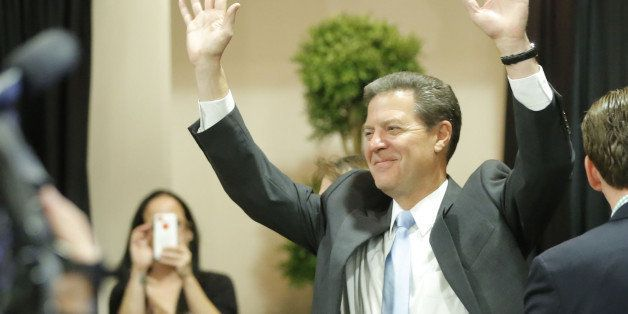 Kansas Gov. Sam Brownback emerges to a cheering crowd in Topeka , Kan., on Tuesday, Nov. 4, 2014, after he was re-elected. (T
