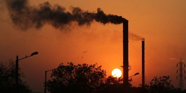 Birds fly past at sun set as smoke emits from a chimney at a factory in Ahmadabad, India, Monday, Dec. 8, 2014. The momentum