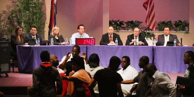FERGUSON, MO - SEPTEMBER 09:  Mayor James Knowles (seated R) ) and city council members wait until angry residents are calmed