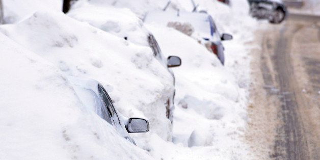 A line of cars sit buried in snow banks in Somerville, Mass., Tuesday, Feb. 10, 2015. The latest snowstorm left the Boston ar