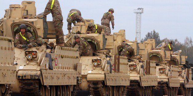 Members of the US Army 1st Brigade, 1st Cavalry Division, transport heavy combat equipment including Bradley Fighting Vehicle