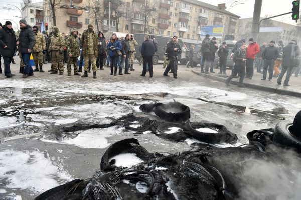 Fighters of the Aydar Ukrainian volunteer battalion, look on after burning tyres at the entrance to the Ukrainian Defence Min