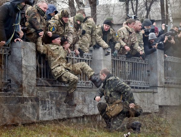 A guard attempts to arrest a fighter of the Ayda Ukrainian volunteer battalion, who entered the compound of the Ukrainian Def