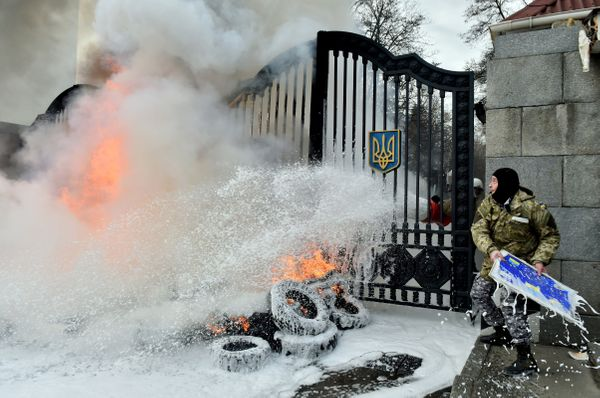 A Ukrainian serviceman throws a signboard over the gates as the flames are doused after fighters of the Aydar Ukrainian volun