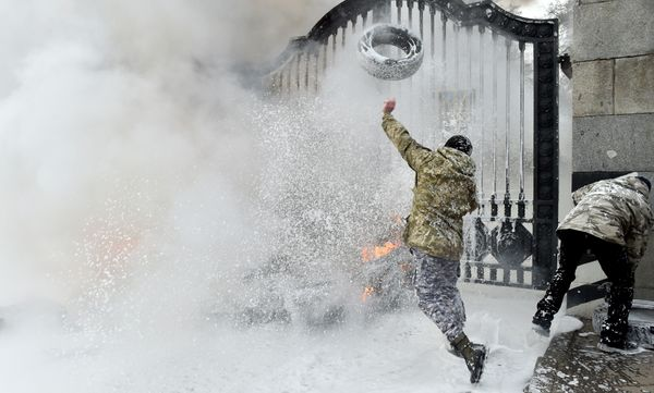 A Ukrainian serviceman throws a tyre over the gates as the flames are doused by firefighters after fighters of the Aydar Ukra
