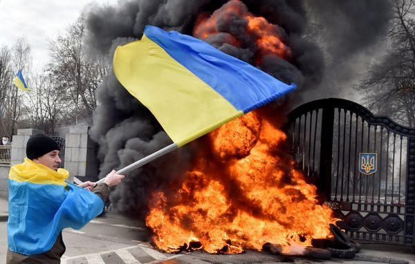 A Ukrainian serviceman waves the national flag as fighters of the Aydar Ukrainian volunteer battalion, burn tyres at the entr