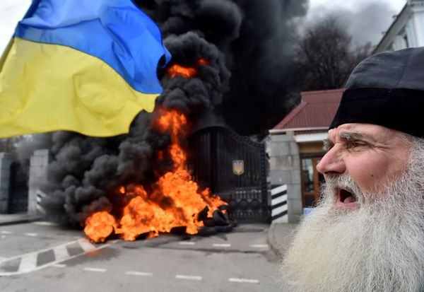 An elderly Orthodox priest shouts as fighters of the Aydar Ukrainian volunteer battalion, burn tyres at the entrance to the U