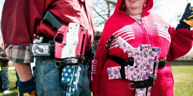 ROMULUS, MI - APRIL 27: Chris (right) and Marty Welch of Cadillac, Michigan, carry decorated Olympic Arms .223 pistols at a r