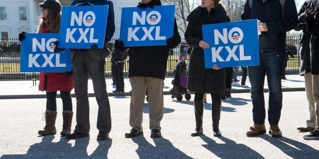 Demonstrators hold signs against the proposed Keystone XL pipeline from Canada to the Gulf of Mexico in front of the White Ho