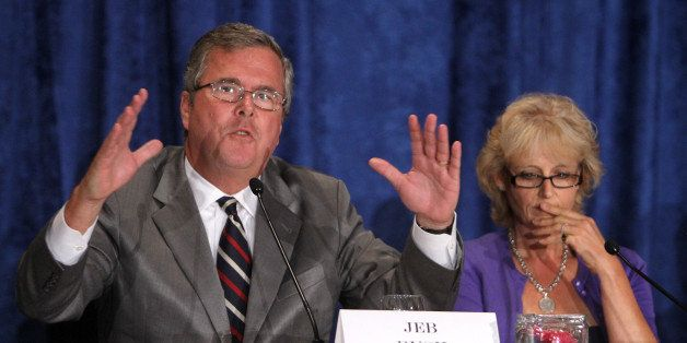 Former Florida governor Jeb Bush, left, makes a point as Kathleen Oropeza, the Orlando mother who helped create the Fund Educ