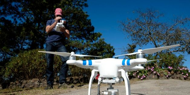 A man with a camera equipped radio controlled quadcopter drone