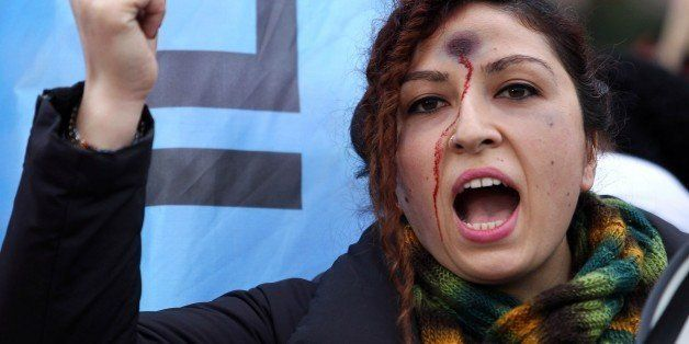 A woman with a bullet hole painted on her forehead takes part in a demonstration against  the murder of 20-year-old Ozgecan A