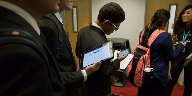 Students view mobile devices while waiting to speak to a representative at the International Business Machine Corp. (IBM) boo