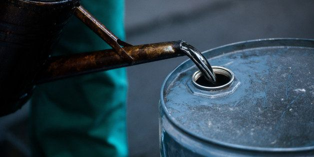 FILE PHOTO: A worker pours liquid oil into a barrel at the delayed coker unit of the Duna oil refinery operated by MOL Hungar